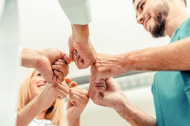 Personalvermittlung Pflegefachkräfte – männliche Pflegekraft bildet mit Fäusten von Teamkollegen einen Kreis